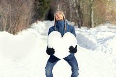 Homem engraçado com a grande dificuldade que mantém o coração enorme feito da neve, estando na estrada nevado no parque do invern fotografia de stock