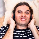 Homem engraçado com música de escuta dos auscultadores Foto de Stock Royalty Free