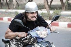 Homem engraçado com um capacete que monta uma motocicleta Fotografia de Stock