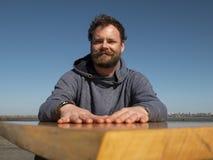 Homem engraçado com uma barba e um bigode que sentam-se em uma mesa de centro contra um céu azul imagens de stock