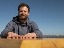 Homem engraçado com uma barba e um bigode que sentam-se em uma mesa de centro contra um céu azul fotos de stock