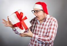 Homem engraçado em um chapéu Santa com um presente de Natal em sua mão Imagem de Stock