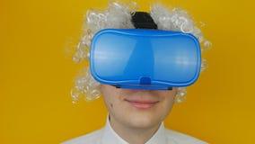 Homem engraçado encaracolado com cabelo branco na emoção dos auriculares da realidade virtual, a cômico e a alegremente humana, n vídeos de arquivo