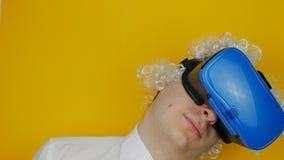 Homem engraçado encaracolado com cabelo branco na emoção dos auriculares da realidade virtual, a cômico e a alegremente humana, n filme