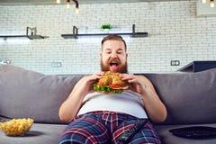 Homem engraçado gordo nos pijamas que come um hamburguer no sofá em casa foto de stock royalty free