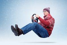 Homem engraçado na camiseta, no lenço e no chapéu, conduzindo o carro com o volante inverno, neve, blizzard fotografia de stock royalty free