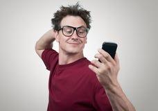 Homem engraçado que fotografa-se em um smartphone Imagem de Stock