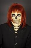 Homem engraçado na máscara um crânio e uma peruca Imagens de Stock