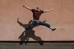 Homem entusiasmado alegre do moderno que salta altamente exterior foto de stock royalty free
