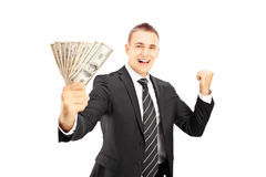 Homem entusiasmado no terno preto que guarda dólares e que gesticula happines Fotos de Stock