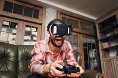 Homem entusiasmado que joga o jogo de vídeo em vidros do vr Fotos de Stock Royalty Free