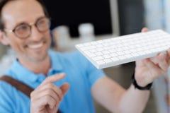 Homem entusiasmado que olha o teclado para seu computador na sala de exposições foto de stock