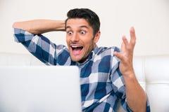 Homem entusiasmado que senta-se no sofá com portátil Imagem de Stock Royalty Free