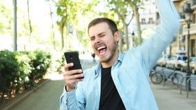 Homem entusiasmado que usa o telefone e os olhares na câmera filme