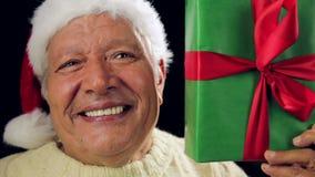 Homem envelhecido alegre com Santa Hat Showing um presente verde filme