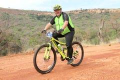 Homem envelhecido de sorriso que aprecia fora o passeio na raça do Mountain bike Imagens de Stock Royalty Free
