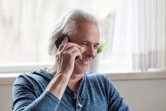 Homem envelhecido feliz que tem a conversação engraçada no telefone foto de stock