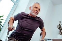 Homem envelhecido forte que tenta andar com muletas fotografia de stock royalty free
