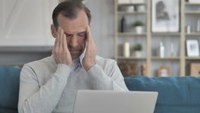 Homem envelhecido médio com funcionamento da dor de cabeça no portátil ao sentar-se no sofá vídeos de arquivo