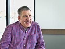 Homem envelhecido médio considerável na roupa ocasional com sorriso na cafetaria fotografia de stock royalty free