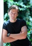 Homem envelhecido médio considerável que inclina-se de encontro à parede no sol Fotos de Stock Royalty Free