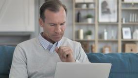 Homem envelhecido médio doente que tosse ao trabalhar no portátil no escritório criativo video estoque