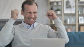 Homem envelhecido médio que comemora o sucesso no portátil no escritório criativo vídeos de arquivo