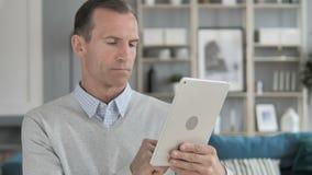Homem envelhecido médio que consulta na tabuleta vídeos de arquivo