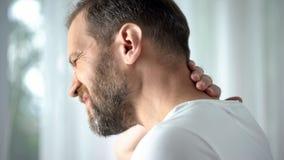 Homem envelhecido médio que faz massagens o pescoço, incômodo de sentimento, problema espinal, cuidado do corpo fotos de stock royalty free