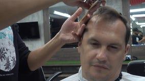 Homem envelhecido médio que faz o corte de cabelo do barbeiro video estoque