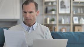 Homem envelhecido médio que faz o documento ao sentar-se no espaço de trabalho criativo filme