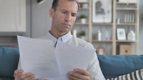 Homem envelhecido médio que lê documentos ao relaxar no sofá filme