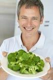 Homem envelhecido médio que prende uma placa dos bróculos imagens de stock