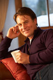 Homem envelhecido médio que relaxa com bebida quente no sofá Foto de Stock