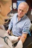 Homem envelhecido médio que tem a análise de sangue feita foto de stock