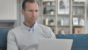 Homem envelhecido médio que trabalha no portátil ao sentar-se no sofá vídeos de arquivo