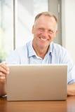 Homem envelhecido médio que usa o portátil em casa imagens de stock
