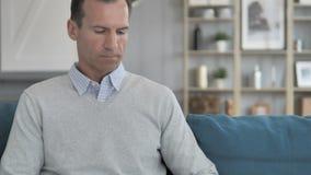 Homem envelhecido médio que vem, sentando e começando o trabalho no portátil vídeos de arquivo