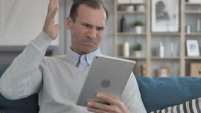 Homem envelhecido médio querendo saber em choque pela perda ao usar a tabuleta vídeos de arquivo