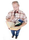 Homem envelhecido meio que lê um livro Fotos de Stock