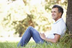 Homem envelhecido meio que relaxa no campo que inclina-se contra a árvore fotos de stock royalty free