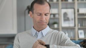 Homem envelhecido meio que usa o smartwatch vídeos de arquivo