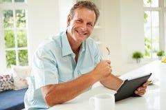 Homem envelhecido meio que usa a tabuleta de Digitas sobre o café da manhã fotografia de stock