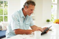 Homem envelhecido meio que usa a tabuleta de Digitas sobre o café da manhã imagem de stock royalty free