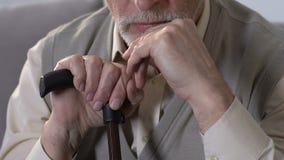 Homem envelhecido pensativo com o bastão que senta-se no sofá e que toca no queixo, problemas de saúde vídeos de arquivo