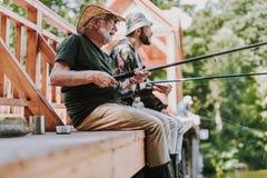 Homem envelhecido positivo que aprecia a pesca com seu filho fotografia de stock
