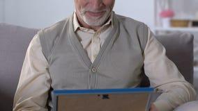 Homem envelhecido que abraça a foto de família no quadro, recordando parentes, memórias agradáveis vídeos de arquivo