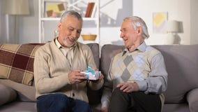 Homem envelhecido que apresenta a caixa de presente do aniversário ao amigo de sorriso, celebração em casa filme