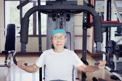 Homem envelhecido que exercita com máquina do peso Imagem de Stock Royalty Free