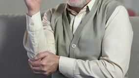 Homem envelhecido que faz massagens o cotovelo, inflamações das junções, doença da artrite, cuidados médicos vídeos de arquivo